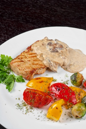 pork steak with mushroom sauce and grilled vegetables photo