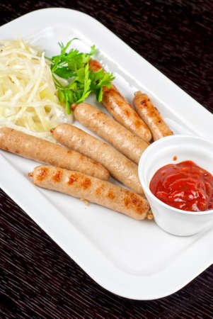 Grilled sausages with cabbage, greens and tomato sauce on white plate photo