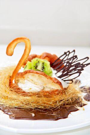 The swan shaped sweet cake closeup at plate photo