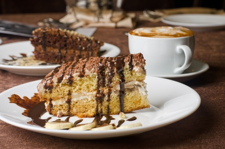 Dessert cakes with banana and coffee at table photo