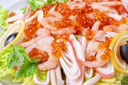 Salad with shrimps, caviar, calamaries, lettuce, lemon and olive photo