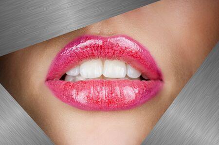 Beautiful female lips closeup behind silver metal background