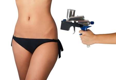 perfect woman body closeup and hand with tanning gun for quick tanning on a white background Stock Photo