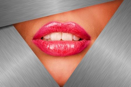 Beautiful female lips closeup behind silver metal background photo