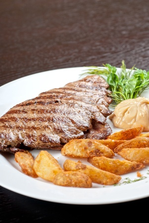 potato leaves: Juicy beef steak stuffed with beef tongue and cheese served with potatoes, greenery and sauce Stock Photo