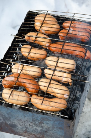grilled sausages on grill, with smoke above it photo