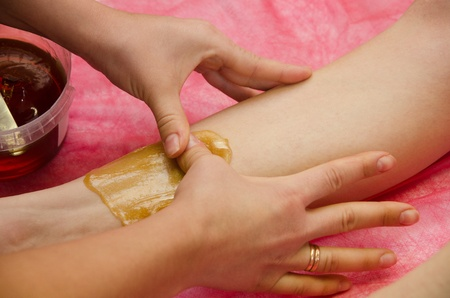 Sugaring: epilation with liquate sugar at legs. It is less painful hair removal with wax replacement