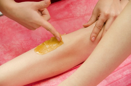 Sugaring: epilation with liquate sugar at legs. It is less painful hair removal with wax replacement photo