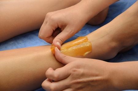 Sugaring: epilation with liquate sugar at legs.