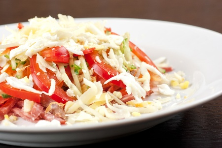 Salad from beef tongue, cervelat, chicken meat, fresh tomatoes, cucumbers, pepper, eggs, cheese and mayonnaise photo