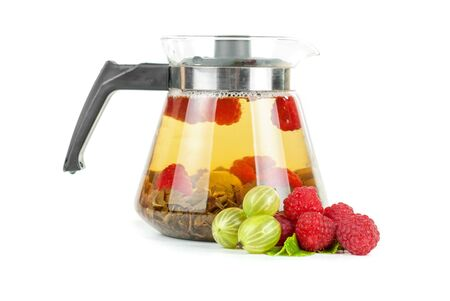 Teapot with fruit tea and berries on a white background photo