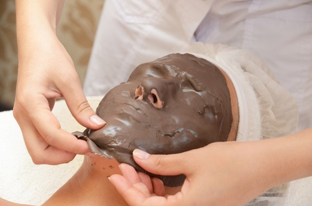Closeup of Chocolate mask at woman face photo