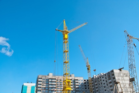 concrete commercial block: Building crane and building under construction against blue sky