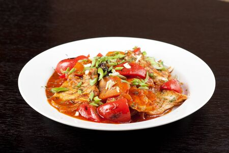 pork meat with tomato, pepper, prunes, garlic and green onion photo