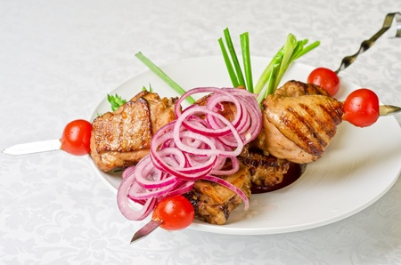 turkish bread: Grilled kebab meat with onion and tomato on a white plate