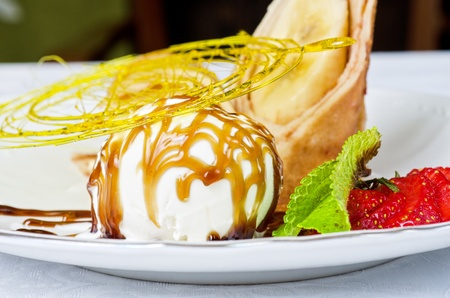 Dessert of pancake with banana, ice-cream, caramel, strawberry and mint photo