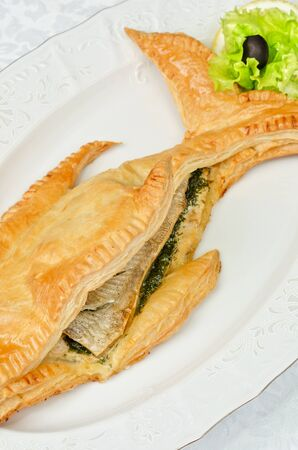 tasty dish of trout fish baked with greens at dough photo