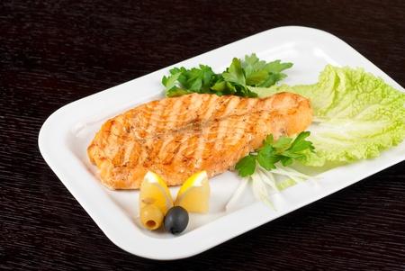 Filetto di salmone alla griglia con verdure, cipolla, limone, lime e olive Archivio Fotografico