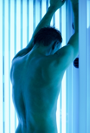 young man closeup at tanning solarium light on Stock Photo