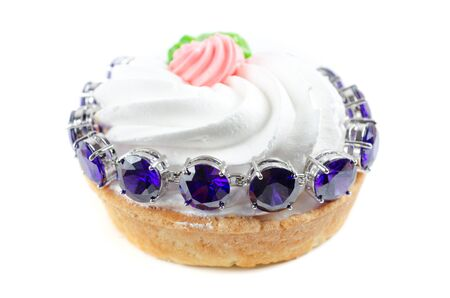 cupcake and bijouterie bracelet with blue gems on a white background photo
