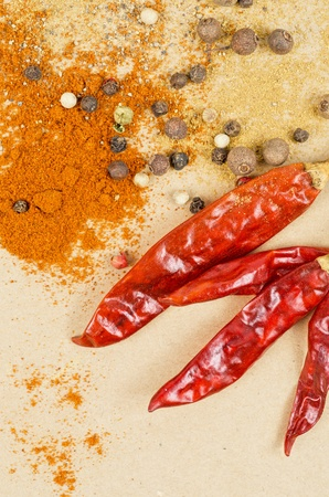 dried peppers and other kind of peppers spices on a brown background photo