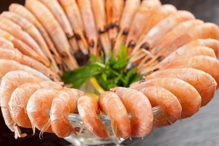 tasty shrimps with lemon and greens closeup photo