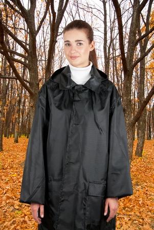 woman in rain coat walking at autumn forest photo