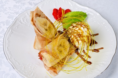 Dessert of pancake with banana, ice-cream, caramel, strawberry and mint photo
