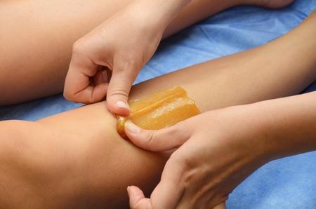Zuccheraggio: depilazione con lo zucchero liquate a gambe.