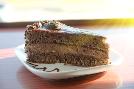 piece of chocolate cake at white plate photo