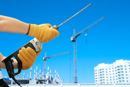 Construction worker building with drill on a building background photo