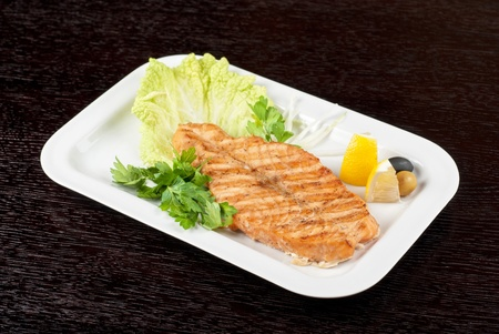 Grilled salmon steak with greens,onion, lemon, lime and olive photo