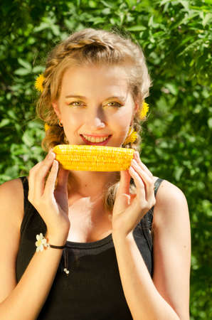 Close-up outdoor portrait of young beauty woman eating corn-cob Stock Photo - 11407685