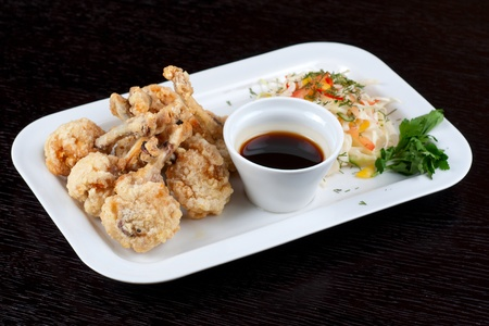 Fried chicken wings garnished with fresh vegetables with Teriyaki sauce photo