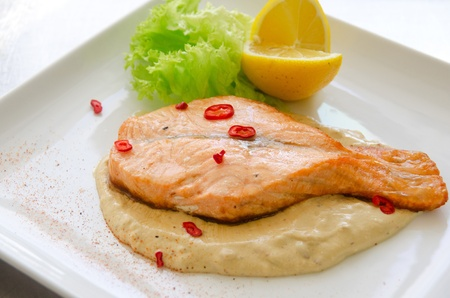 Grilled salmon steak with greens, lemon, sauce and pepper chile photo