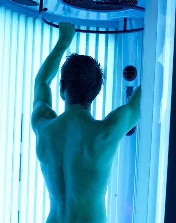 young man closeup at tanning solarium light on Stock Photo