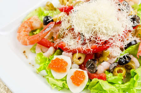 Salad with shrimps, eggs, caviar, calamaries, lettuce, olive, tomato and mozzarella photo