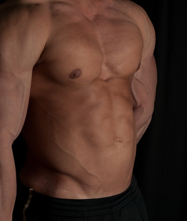 Muscular male torso of bodybuilder on black background photo
