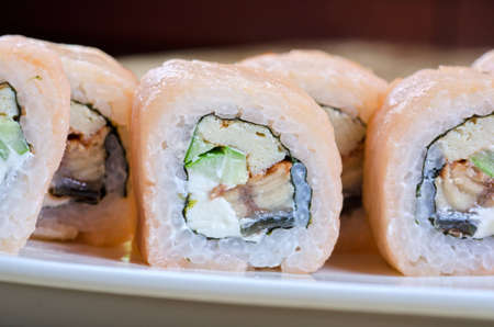 sushi roll of shrimp, eel, cucumber, pepper and sauce photo