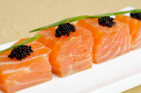 Salmon Slices with black tobiko caviar and greens photo