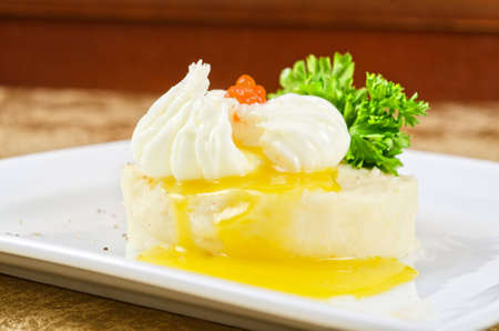 poached eggs in a nest of mashed potatoes with greens and caviar photo