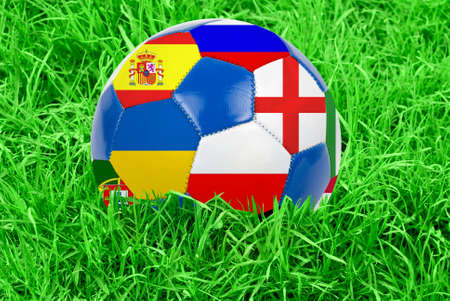 Soccer ball on grass field background  Ball filled with euro 2012 countries flags colors  photo