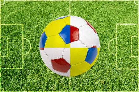 Soccer ball colored by flag of Poland and Ukraine at green grass photo