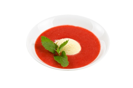 Strawberry soup with ice cream and mint on a white photo