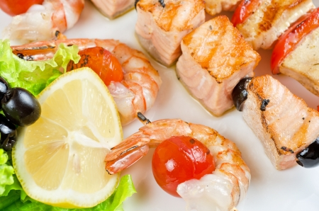 Closeup of grilled shrimps and tomatoes on bamboo sticks with salmon photo