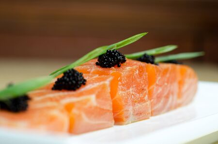 Salmon Slices with black tobiko caviar and greens Stock Photo - 13657340