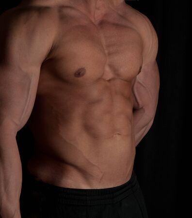 Muscular male torso of bodybuilder on black background photo