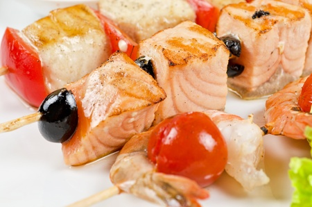 Closeup of grilled salmon and shrimps with tomatoes and peppers on bamboo sticks photo