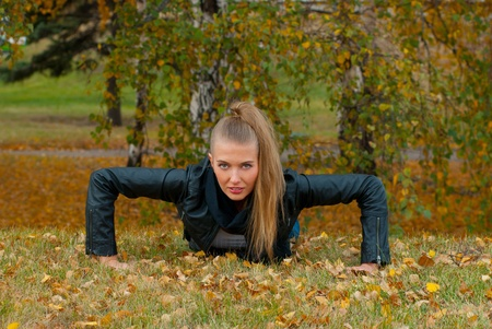Beauty female doing push ups in the park photo