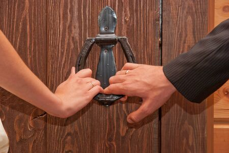 Close up of just married hands opening the door together photo